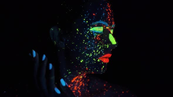 Thumbnail for Paint Glowing in Ultraviolet Light. Portrait of a Girl Painted with Glowing Paint