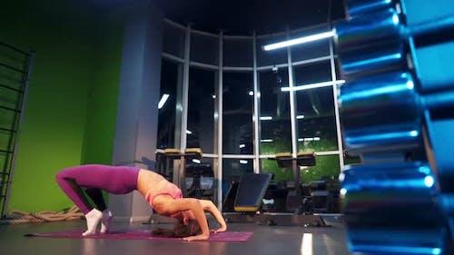 Female doing yoga in a studio. Model with long hair makes a yoga bridge