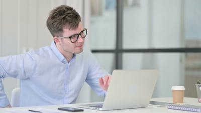 Young Man with Laptop Having Back Pain