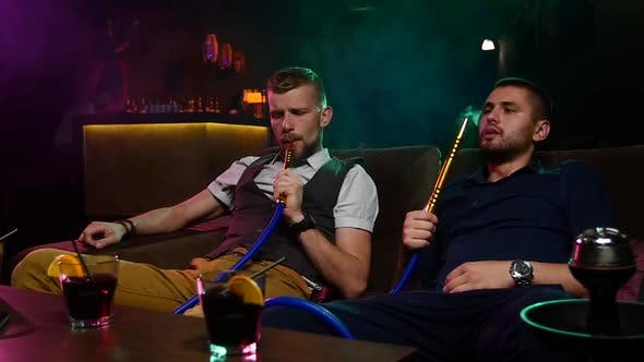 Two Young Men Smoke From Shisha Pipe. Slow Motion