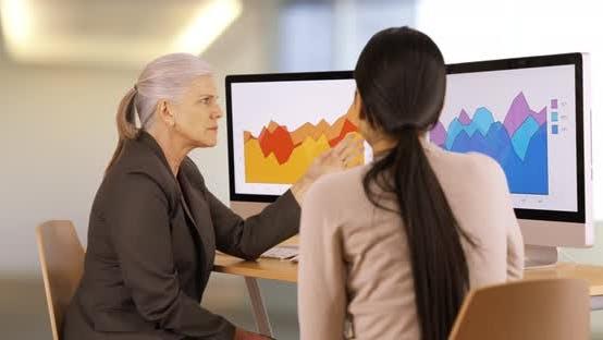 Thumbnail for Two businesswomen discuss graphs
