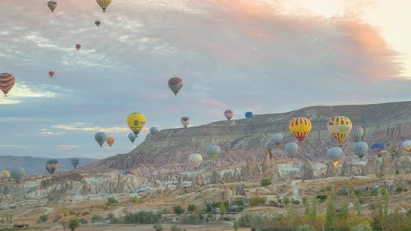 Colorful hot air balloons flying over rock landscape at Goreme, Cappadocia, Turkey