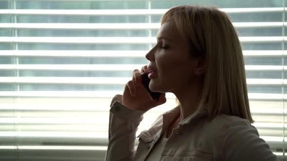 Junge Blonde Frau spricht mit dem Handy und tratscht mit Freund oder Kollegen