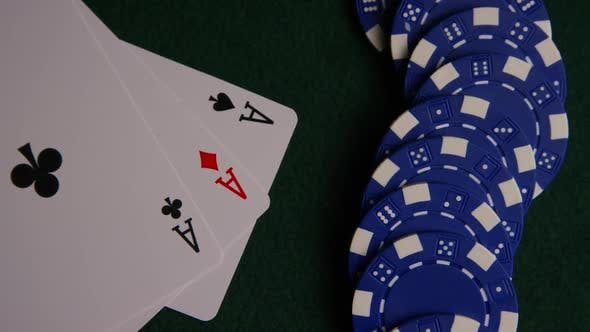 Rotating shot of poker cards and poker chips on a green felt surface - POKER 052