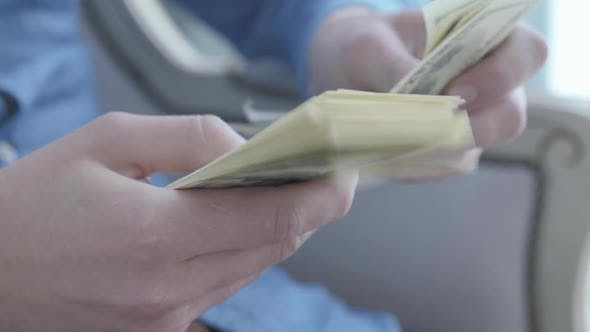 Thumbnail for Close Up Hands of the Young Man in Blue Shirt Sitting in the Armchair Counting Money