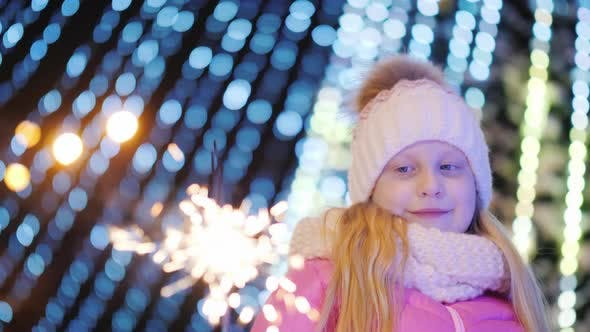 Girl Playing with Sparkler on the Background of Blurry Lights of a Large Christmas Tree