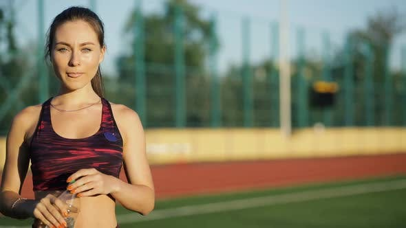 Thumbnail for Young Sportswoman Drinking Water From Bottle on Stadium Outdoors. Smiling Female in Sportswear