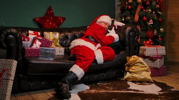 Tired Santa Claus Sleeps on the Couch Wakes Up Checks If Gifts Are on the Spot and Falls Asleep