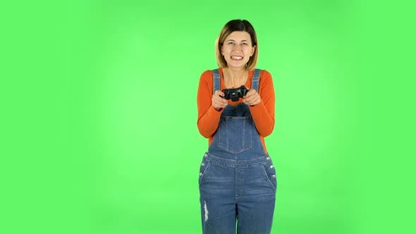 Thumbnail for Girl Playing a Video Game Using a Wireless Controller with Joy and Rejoicing in Victory. Green