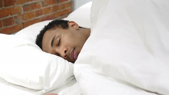 Thumbnail for African Man Sleeping on Side in Bed at Night