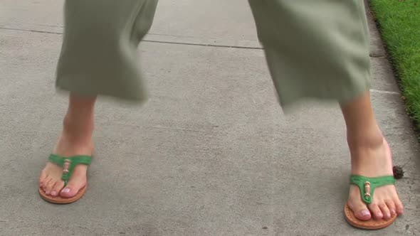 Thumbnail for Young woman jumping on sidewalk with flips flops