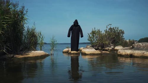 Terrible demon standing in the river. Scary figure in black mantle.
