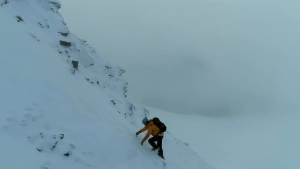 Thumbnail for Mountaineer Using a Pick to Climb a Snowy Mountain