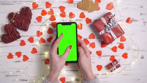 Valentinstag eine Frau benutzt ein Smartphone mit einem Greenscreen Closeup Draufsicht