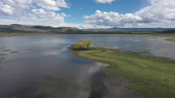 Thumbnail for Aerial view of marsh lake in Oregon with trees on peninsula