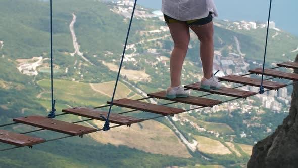 Thumbnail for Woman Walking By Suspension Bridge