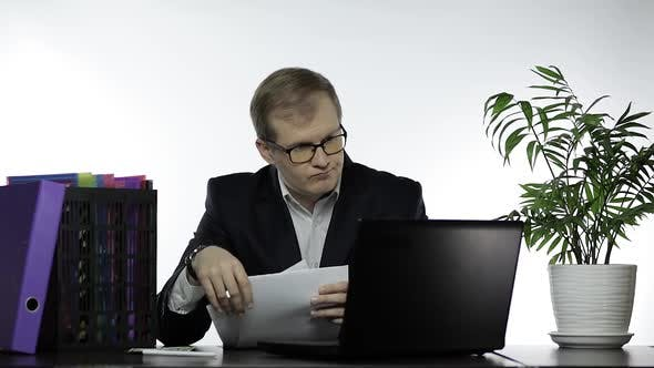 Thumbnail for Businessman Working in Office. Reading Papers at Table and Work on Laptop