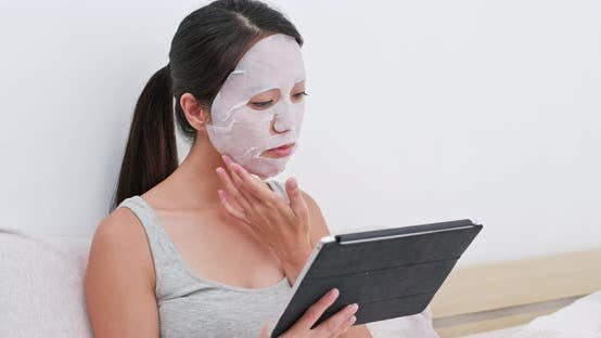 Thumbnail for Frau gelten Gesichtsmaske und beobachten auf Tablette zu Hause