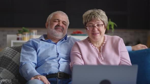 Glücklicher Großvater und Großmutter kommunizieren per Online-Video-Chat mit Freunden oder Kindern