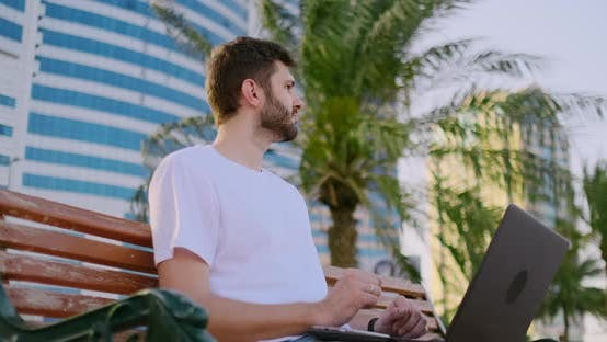 Thumbnail for A Young Man in the Summer of Palm Trees Sitting with a Laptop and Typing on the Keyboard