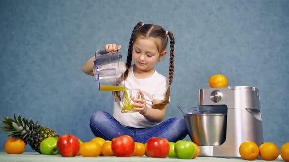 Thumbnail for Girl drinking fresh juice. Little girl pours orange juice into the glass