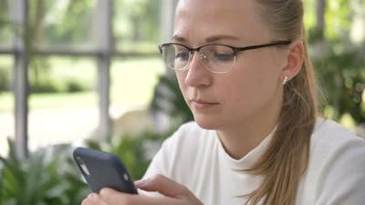 Attractive Woman with Glasses Uses Mobile Phone in Cafe
