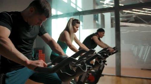 Athlet sitzt auf stationärem Fahrrad in der Nähe seiner Freunde und beginnt zu treten