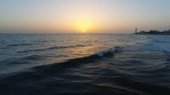 Aerial Flight Above Ocean To Sunset