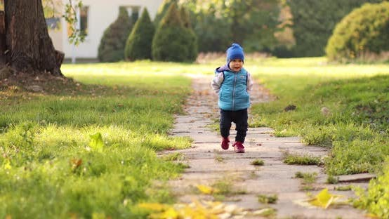 Thumbnail for Alone Toddler in Blue Hat and Vest Walking Away Funnily in Autumn Park
