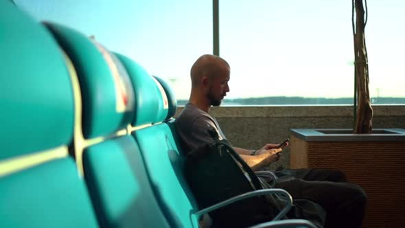 American Businessman Uses Smartphone While Sitting By Window at Airport Room Spbd
