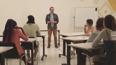 Unrecognizable Students Listening to Male Professor