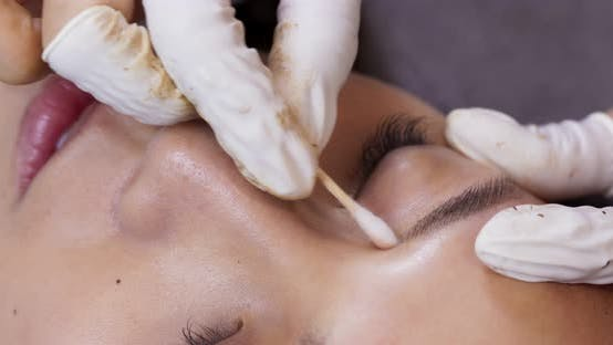 Young woman gets facial beauty procedure, microblading procedure
