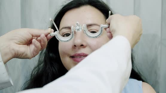 Close Up Eyesight Measurement To Young Woman with Optical Phoropter. Woman Doing Eye Test Slow