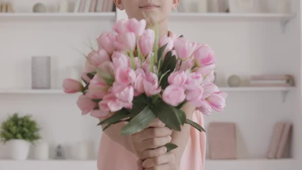 Thumbnail for Unrecognizable Boy Stretching Bouquet of Pink Tulips at Camera. Polite Caucasian Kid Coming for