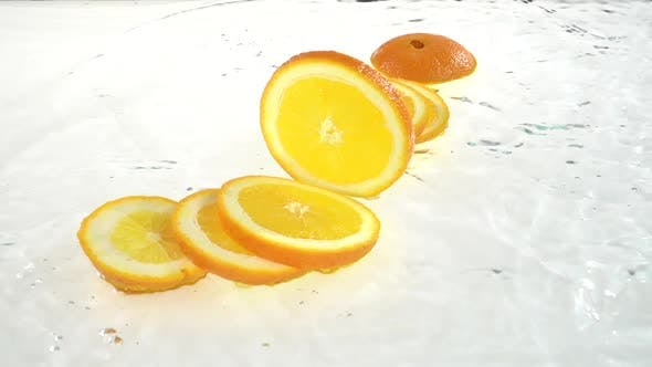 Thumbnail for Orange Falls Into the Water and Flakes To the Lobules. White Background. Slow Motion