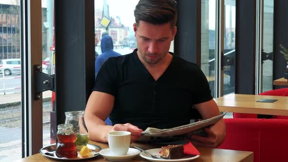 Thumbnail for A Young Handsome Man Sits at a Table with Meal in a Cafe, Reads a Newspaper and Drinks Tea