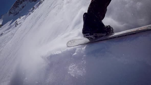 The Legs of a Confident Snowboarder. Athlete Rides on White Snow, Extreme Sports.