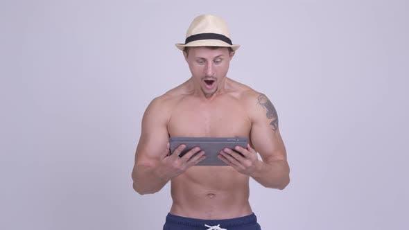 Cover Image for Glückliche muskulöse bärtige Tourist Man mit Digital Tablet und Getting Good News