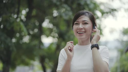 woman walking and listening to music with wireless headphones
