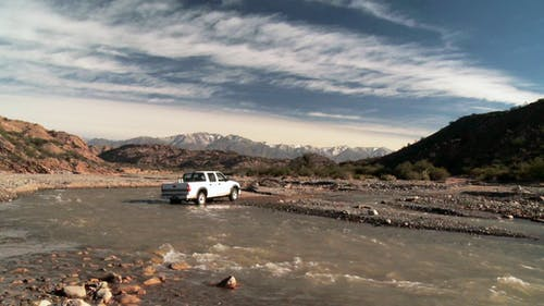 Four-wheel drive Pickup Truck Crossing a River near the Andes Mountains, Argentina, South America.