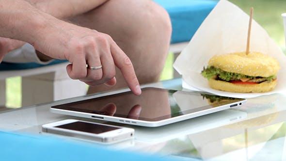 Thumbnail for Junger Mann verwendet Tablet im Freien