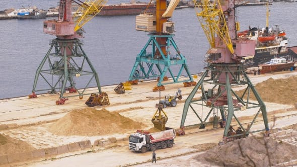 Thumbnail for Industrial Port Area. Crane With Bucket Loads Mortar Sand in the Truck.