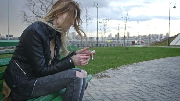 Thumbnail for Dissapointed Girl With Long Blonde Hair In Leather Jacket Straightens Hair Use Gadget