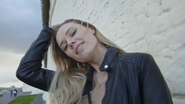 Thumbnail for Girl With Long Blonde Hair In Leather Jacket Posing In The City Straightens Hair