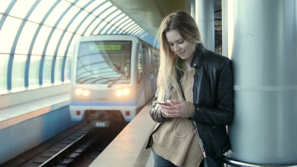 Thumbnail for Cute Girl With Gadget Long Blonde Hair In Leather Jacket With Straightens Hair Standing In Metro