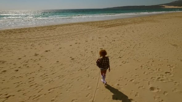 Thumbnail for Young Woman Walking Alone Along a Beach