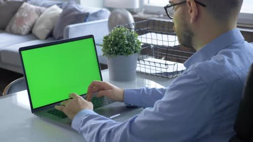 Man Uses Laptop with Green Mock-up Screen While Sitting at the Desk in His Cozy Living Room
