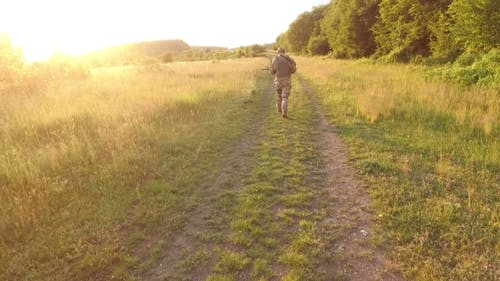 Aerial View: Soldier Goes On Path In The Field. Camera Behind Him