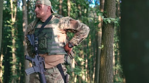 Military Putting On Military Equipment In The Forest