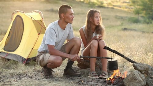 Couple At The Camping With Campfire